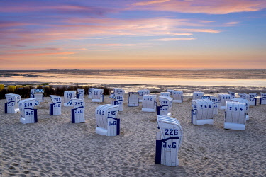 GER10205AW Duhnen, Cuxhaven, Lower Saxony, Germany. Strandkorb beach chairs and the Wadden Sea at sunset.