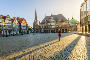 GER10229AW Bremen, Bremen State, Germany.  Adult man walking in Marktplatz at sunrise looking at the Town Hall (MR)
