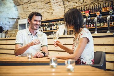 ITA11043AW Astino, Bergamo province, Lombardy, Italy. Couple drinking wine in a wine cellar (MR).