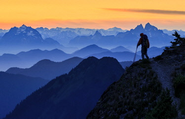 US48GLU0991 USA, Washington State. A backpacker descending from the Skyline Divide in the North Cascades near Mt. Baker at sunset. Prominent peaks are Judge Howay and Robie Reid in Canada. Digital composite. (MR)