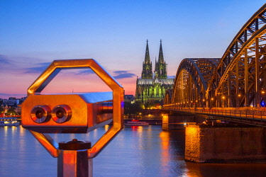 CLKAB60840 Hohenzoller Bridge over River Rhine and Cologne Cathedral with binoculars at dusk in Cologne city. Cologne city (Koln), North Rhine Westphalia, Germany, Europe.