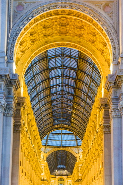 ITA11177AW Milan, Lombardy, Italy. The entrance to the Galleria Vittorio Emanuele II illuminated at dusk.