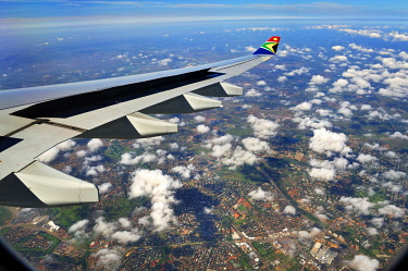 IBLABC03985394 Wing of an Airbus in flight, with winglet and the logo of SAA, South African Airways, suburbs of Johannesburg at the back, South Africa, Africa