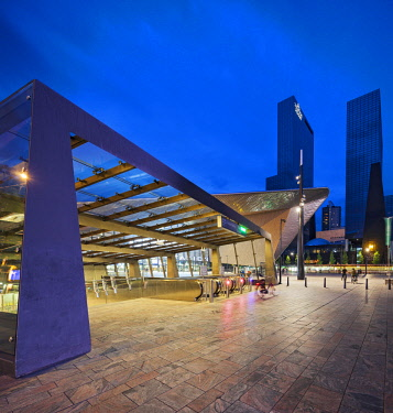 NLD0535 Entrance to Rotterdam Centraal Station with the Gebouw Delftse Poort Building in the background at twilight, Weena, Rotterdam, Zuid Holland, The Netherlands.