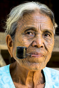 IBLDBF03896058 Woman of the Chin people, ethnic minority, with a traditional facial tattoo smoking a pipe, the last of their kind, portrait, Rakhine State, Myanmar, Asia