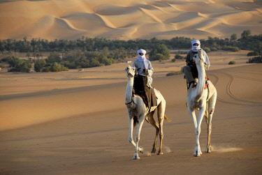 ibxaut00217047 Two Tuareg ride elegantly on their camels in the desert Mandara, Libyan Desert, Sahara,  Libya, Africa