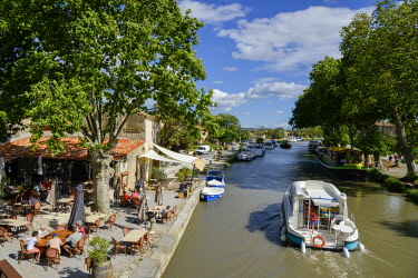 HMS2068577 France, Aude, Saint Nazaire d'Aude, Canal du Midi listed as World Heritage by UNESCO, Port of Somail, boat of tourism passing in front of an open air dance hall in border of water