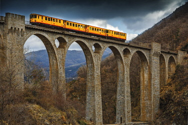 HMS3090273 France, Pyrenees Orientales, Natural regional park Catalan Pyrenees, Tet Valley, Sejourne bridge, Le Train Jaune, rain crossing the bridge Sejourne in winter
