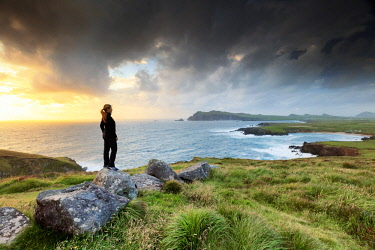 IRL0840AW Europe, Ireland, Kerry, Dingle peninsula, woman looking towards Ballyferriter Bay from Clougher Head at sunset, MR