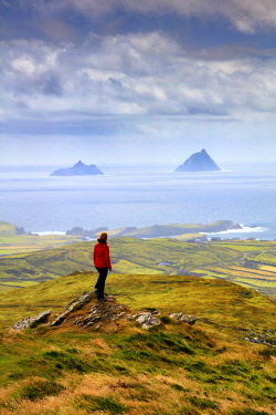 IRL0864AW Europe, Ireland, ring of Kerry, Woman with red jacket on a viewpoint on Valentia island with Skellig islands in the background, MR