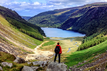 IRL0923AW Europe, Ireland, Wicklow, woman alone looking the valley and Glendalough lake, MR