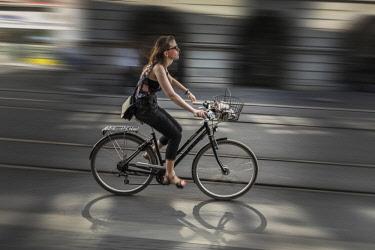 SWI8012AW Europe, Switzerland, Zurich, Niederdorf, Woman riding a bicycle.