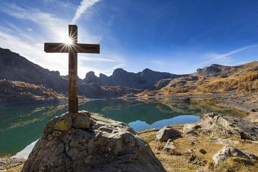 HMS2150535 France, Alpes de Haute Provence, Parc National du Mercantour (National park of Mercantour), Haut Verdon, wooden cross by the lake of Allos (2 228m) in autumn, in the background of impressive towers of...