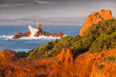 HMS2881435 France, Var, Saint Raphael, heavy swell and high winds on the red cliffs of volcanic origin (rhyolite) of the Cap du Dramont, in background the tower of the ile d'Or