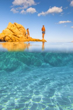 CLKAB68786 A couple relaxing admiring the view and the crystal turquoise water standing on rocks in Capriccioli beach, Arzachena Costa Smeralda, Olbia-Tempio province, Sardinia district, Italy
