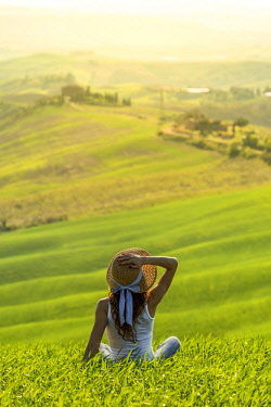 CLKAC66513 Orcia valley, Siena, Tuscany, Italy. A young woman with straw hat admiring the view on a wheat field (MR)