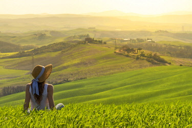 CLKAC66514 Orcia valley, Siena, Tuscany, Italy. A young woman with straw hat admiring the view on a wheat field (MR)