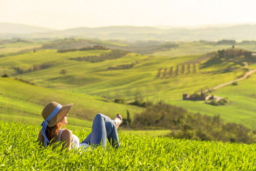 CLKAC66516 Orcia valley, Siena, Tuscany, Italy. A young woman with straw hat relaxing on a wheat field (MR)