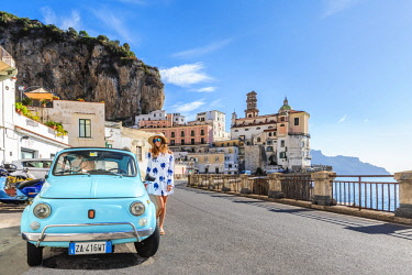 CLKAC69733 Atrani, Amalfi coast, Salerno, Campania, Italy. Young woman with her blue Fiat 500 (MR)