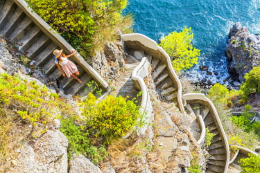 CLKAC69750 Praiano, Amalfi coast, Salerno, Campania, Italy. Girl goes down along a stairway to the sea (MR)