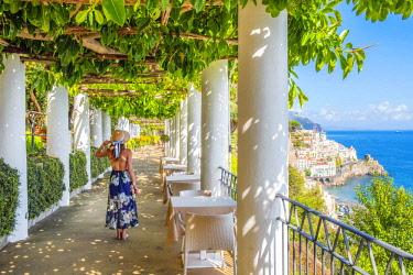 CLKAC69952 Amalfi, Amalfi coast, Salerno, Campania, Italy. A lady walking along a terrace. Amalfi village in background (MR)