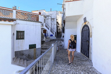 CLKFB68154 A girl walks among the white houses of the old town of Rodi Garganico, Apulia(Puglia), Italy. (MR)