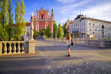 CLKST67161 A girl walking in the old town of Ljubljana, with the Triple Bridge and the iconic Franciscan Annunciation Church on the background. Ljubljiana, Osrednjeslovenska, Slovenia.