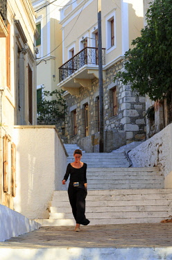Greece, Symi, Chorio. Woman walking down the Kali Strata steps between the Old Town and Harbour.