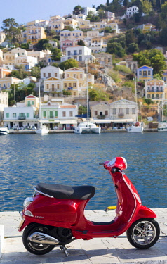 GRE1586AW Greece, Symi, Yialos. Red Vespa Scooter parked beside the harbour.