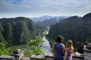 VIT1408AW Asia, South East Asia, Vietnam, Ninh Binh, Tam Coc, a traveller couple looking out from an elevated view of the karst limestone hills of Tam Coc and the Ngo Dong River from the 15th Century Bich Dong...