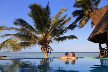 TZ02282 Tanzania. Zanzibar, Kigomani, Couple relaxing inside infinity pool overlooking the beach at luxurious resort (MR)