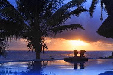 TZ02365 Tanzania. Zanzibar, Kigomani, Couple relaxing inside infinity pool overlooking the beach at luxurious resort (MR)