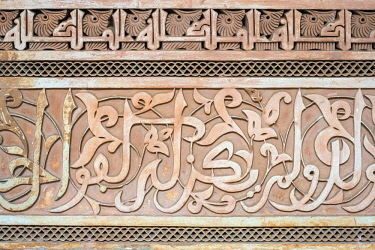 MOR2373AW Morocco, Marrakech-Safi (Marrakesh-Tensift-El Haouz) region, Marrakesh. Carved plaster arabic calligraphy, Ben Youssef Madrasa, 16th century Islamic college.