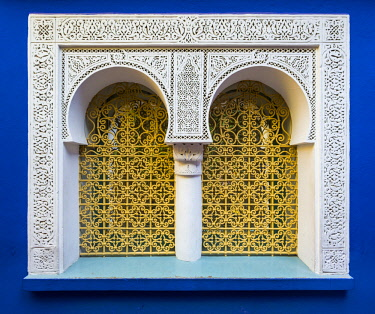 MOR2380AW Morocco, Marrakech-Safi (Marrakesh-Tensift-El Haouz) region, Marrakesh. Ornate window against blue wall at Jardin Majorelle gardens.