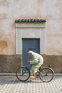 Morocco, Marrakech-Safi (Marrakesh-Tensift-El Haouz) region, Marrakesh. A man wearing a djellaba walks past a decorative doorway in the medina (old town).
