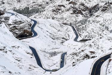 MOR2441AW Morocco, Marrakech-Safi (Marrakesh-Tensift-El Haouz), Al Haouz Province. Winding road through Tizi N'Tichka pass in the Atlas Mountains during winter snow.