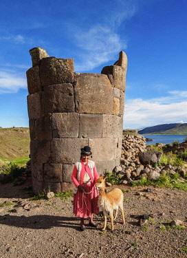 PER34213AW Native Lady with Vicuna in front of the Chullpa, Sillustani, Puno Region, Peru