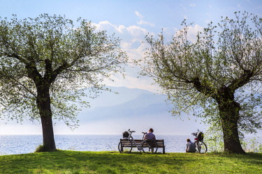 A bicycle couple relaxes in front of the panorama of Lake Garda in Malcesine, Italy