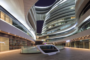 CH1396 The Galaxy Soho building comprises four main domed structures, fused together by bridges and platforms between curving floor plates to create a fluid environment that surrounds a series of public cour...