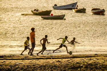 IBLDRN04474935 Teenager playing soccer, children, evening mood, city beach of Tarrafal, Sao Nicolau, Cape Verde, Africa