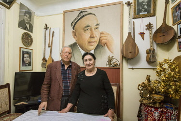UZB0034AW Hasan Rajabiy (Khassan Rajabi) and wife, son of the legendary uzbek composer Yunus Rajabiy, near the painting of his father. He is a player of Shashmaqam, a sort of music with lyrics derived from Sufi...