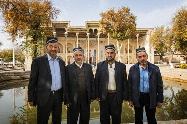 UZB0065AW Uzbek men. In the background the Bolo Hauz Mosque. Bukhara, a UNESCO World Heritage Site. Uzbekistan
