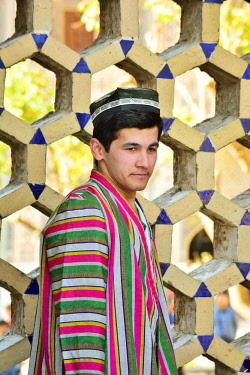 UZB0148AW A groom wearing the traditional outfit. Registan square, a UNESCO World Heritage Site, Samarkand. Uzbekistan