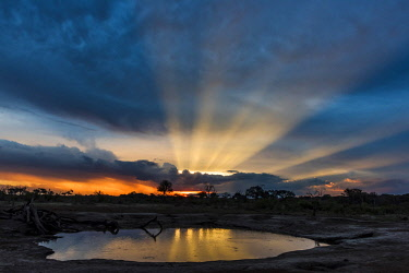 ZIM2644AW Africa, Zimbabwe, Hwange National park.  View across a waterhole at sunbeams bursting out above cumulus clouds at sunset