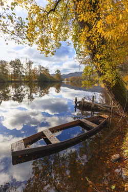 FRA10199AW A wooden rowing boat in autumn on the Dordogne River,  Correze, Nouvelle-Aquitaine, France