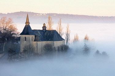 FRA10216AWRF Collégiale Notre Dame et St Pantaléon de Turenne in the mist at sunset, Correze; Nouvelle-Aquitaine; France;