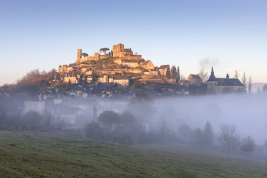 FRA10205AW Hilltop village of Turenne surrounded by mist, Correze; Nouvelle-Aquitaine; France; West Europe