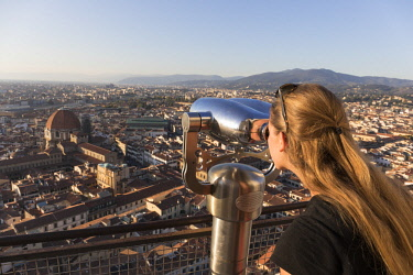 ITA11385AW A tourist looks through binoculars at the city of Florence, Tuscany, Italy