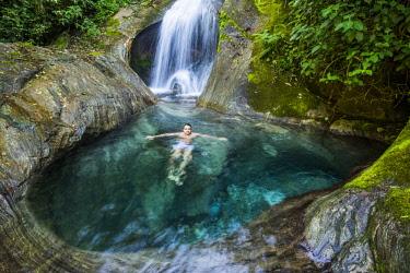 ARBAVI002130 Man swimming in beautiful Atlantic Rainforest river with crystal clear water, Serrinha do Alambari, Rio de Janeiro State, Brazil