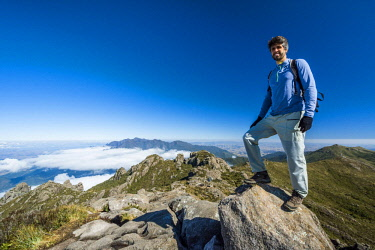 ARBAVI002156 Smiling male hiker standing on summit of Morro do Couto in Mantiqueira Mountains and looking at camera, Itatiaia National Park, Rio de Janeiro State, Brazil